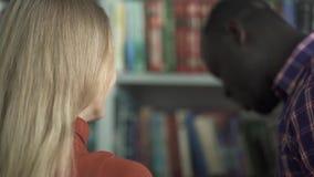 De Europese vrouw en Afrikaanse Amerikaan kiezen een boek in de bibliotheek stock footage