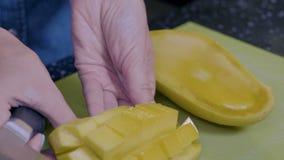 De exotische vruchten worden gesneden in stukken met een mes stock videobeelden