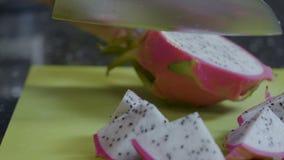 De exotische vruchten worden gesneden in stukken met een mes stock footage