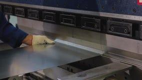 De exploitant neemt een blad van metaal in de buigende machine op en buigt het Het proces van metaalbehandeling Sluit omhoog stock footage