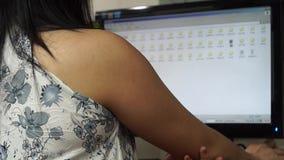De exploitant van de damedesktop doorbladert computer om dossiers te vinden om worden gewerkt op