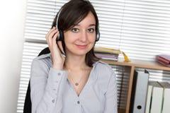 De exploitant van de vrouwenklantenondersteuning met hoofdtelefoon en het glimlachen Royalty-vrije Stock Foto