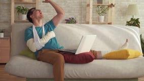 De expressieve jonge mens met een gebroken arm en een been gebruikt laptop en leert over winst langzame mo stock video