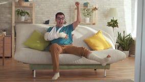 De expressieve jonge mens met een gebroken arm en beenzitting op de laag leert over winst langzame mo stock video