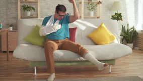 De expressieve jonge mens met een gebroken arm en beenzitting op de laag met een voetbalbal leert over winst stock video