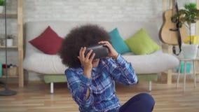 De expressieve positieve Afrikaanse Amerikaanse jonge vrouw gebruikt Vr-glazen en virtuele technologie in woonkamer stock video