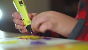 De extra jongen van de close-uptiener gebruikt een 3D pen Hij creeert een 3D cijfer van plastiek stock video
