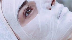 De extreme dichte omhooggaande mening van aantrekkelijke woman's ziet onder het witte kosmetische kleimasker onder ogen Therape stock videobeelden