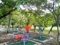 De färgrika utomhus- övningsmaskinerna i parkera är frodiga gröna träd royaltyfria foton