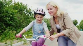 De första framgångarna av barn En kvinna undervisar hennes dotter att rida en cykel, applåderar hennes framgång stock video