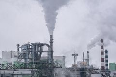 De fabriek geeft heel wat rook en smog van de hemel vrij stock afbeelding