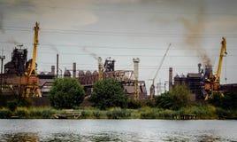 De fabriek met rokende fabriek leidt dichtbij de rivier door buizen tegen een rug Royalty-vrije Stock Foto