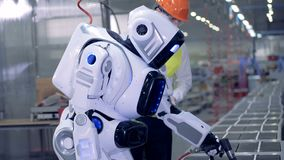 De fabrieksarbeider controleert het droid` s werk, omhoog sluit