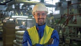 De fabrieksarbeider in een bouwvakker glimlacht bij de camera stock videobeelden