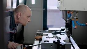 De fabrieksarbeider programmeert een CNC malenmachine stock footage