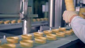 De fabrieksarbeider zet wafeltjekoppen in een bewegende transportband stock videobeelden
