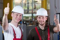De fabrieksarbeiders die duimen geven ondertekenen omhoog stock afbeelding