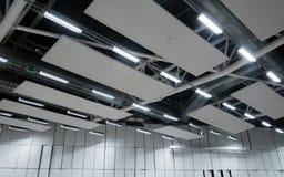 De fabrieksbouw of de pakhuisbouw Enorme lege ruimte met ventilatiepijpen en lichten stock afbeelding