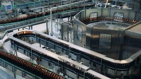 De fabriekslijn beweegt flessen bij een brouwerij stock videobeelden