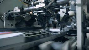 De fabrieksmachine snijdt randen van gedrukte boeken af stock video