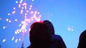 De familie bekijkt de hemel bij het vuurwerk De nachthemel in lichten stock footage