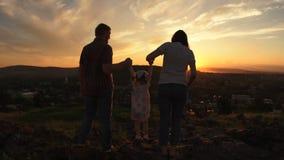 De familie bevindt zich op een heuvel bij zonsondergang op een de zomeravond stock video