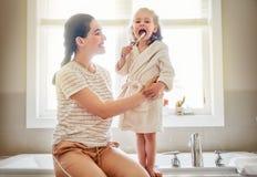 De familie borstelt tanden stock afbeeldingen