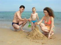 De familie bouwt zandkasteel op strand Stock Afbeelding