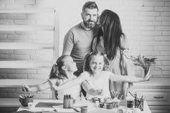 De familie brengt samen tijd door Meisjes die met kleurrijk verven, tellers en potlood op lijst glimlachen royalty-vrije stock fotografie