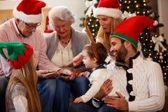 De familie brengt samen tijd op Kerstmisdag door en gebruikt tabl stock foto's