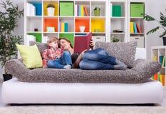 De familie brengt tijd aan het lezen van een boek door royalty-vrije stock foto