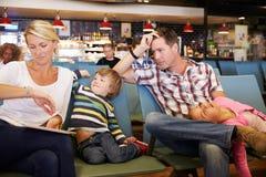 De familie in de Zitkamer van het Luchthavenvertrek wacht op Vertraagde Vlucht royalty-vrije stock foto