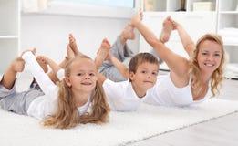 De familie die het uitrekken doet zich oefent thuis uit stock fotografie