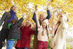 De Familie die van de Multlgeneratie Bladeren in Autumn Garden werpen Royalty-vrije Stock Fotografie