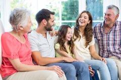 De familie die van meerdere generaties terwijl het zitten op bank glimlachen Royalty-vrije Stock Foto