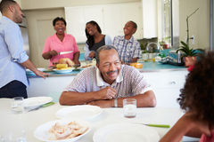 De Familie die van meerdere generaties voor Maaltijd thuis voorbereidingen treft stock afbeelding