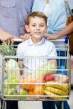 De familie drijft het winkelen karretje met voedsel en jongen die daar zit Stock Foto's