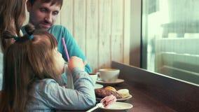 De familie in een koffie, de dochter een milkshake drinken, het mamma en de papa die communiceren stock videobeelden