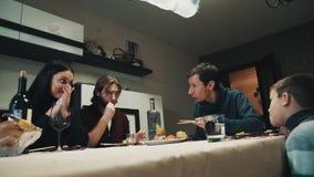 De familie en de vriend bij dinerlijst die en eten sushi, viering spreken stock video