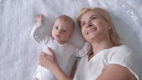 De familie en het geluk, houdende van jonge moeder koesteren en kussen een pasgeboren dochter liggend op witte achtergrond en zie stock footage