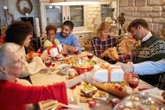 De familie en de vrienden genieten van op samen aanwezig Kerstmisdiner en uitwisseling stock foto