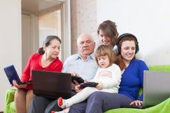De familie gebruikt weinig diverse apparaten in huis Stock Fotografie