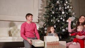 De familie geeft elkaar voorstelt tijdens het Nieuwjaar, zitten zij dichtbij de Kerstboom stock video