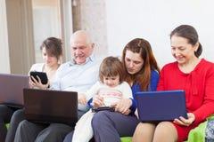 De familie geniet van thuis met weinig laptops Stock Afbeeldingen