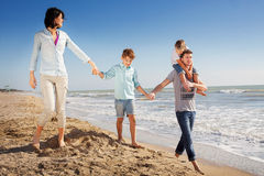 De familie genoot van lopend op het strand bij het overzees royalty-vrije stock afbeeldingen