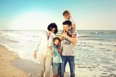De familie genoot van lopend op het strand bij het overzees royalty-vrije stock afbeelding