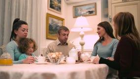 De familie heeft een gesprek terwijl het drinken van thee stock videobeelden