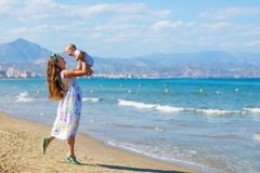 De familie heeft pret bij de kust in zomer Stock Afbeelding