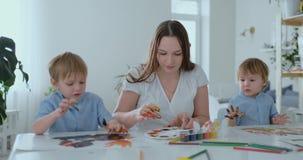 De familie heeft pret het schilderen op papier met hun vingers in verf Mamma en twee kinderenverf met vingers op papier stock videobeelden