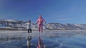 De familie is ijs schaatsend bij dag Meisjes om cijferschaatsen in aard te berijden Moeder en dochter die samen op ijs binnen ber stock video